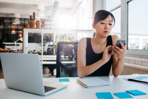 woman in office on smartphone with laptop